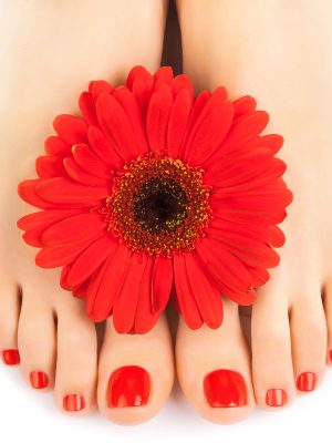 Woman feet  with beautiful red manicured nails
